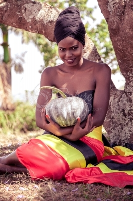 A black uganda woman holding a pumpkin