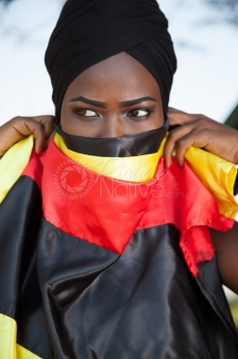 A black woman covering herself with a Uganda flag colors