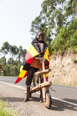 A boy on a wooden bicycle with a Uganda flag