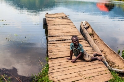 A boy seated at a canoe landing board