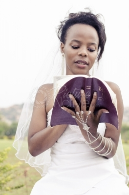 A bride in a gown reading a bible