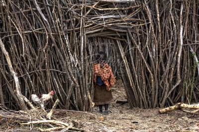 A child emerging out of a secured homestead gate