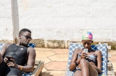 A couple using their phones by the pool side