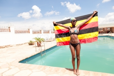 A girl with Uganda flag at the swimming pool
