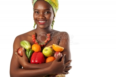 A happy black woman holding fruits and vegetables