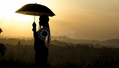 A lady with an umbrella at sunset