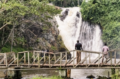 A man and a boy standing on a wooden bridge in front of a waterfall