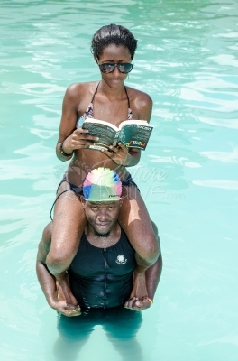A man caryying a woman on his shoulders in a pool