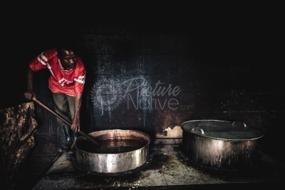 A man cooking food from a dilapidated kitchen