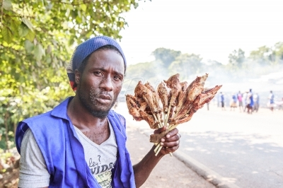 A man holding roasted chicken meat by the roadside