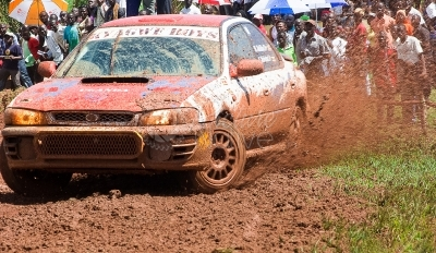 A race car negotiating a muddy terrain