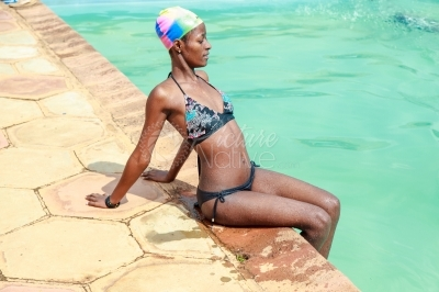 A slender girl seated at the pool side