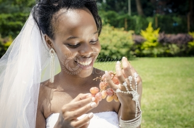 A smiling bride holding grapes