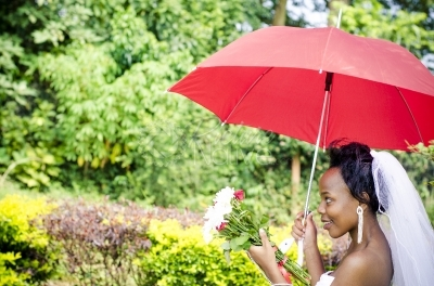 A smiling bride with flowers and red umbrella