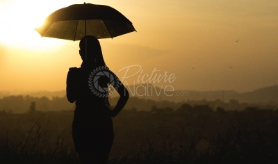 A woman holding an umbrella at sunset