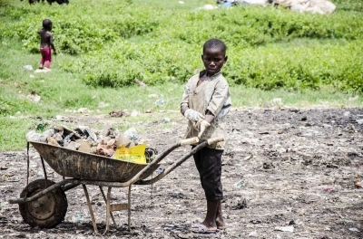 A young boy readys himself to push a loaded wheelbarrow
