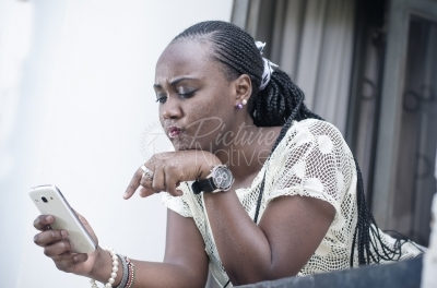 A young lady reacts as she reads a text message from her phone