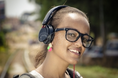 A young lady wearing big headsets and spectacles