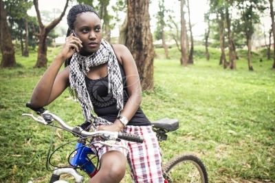 A young woman on bike talking on phone
