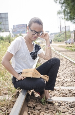 A young woman reading a book from a rail line