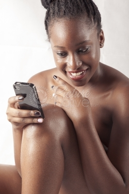 A young woman reading a text message from her phone