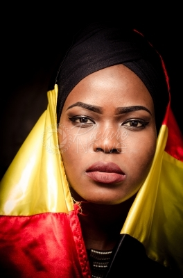 A young woman wrapped in Uganda national colors