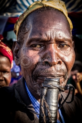 An aged man blowing a horn