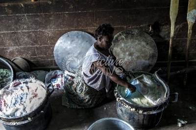An Elderly Lady Preparing Food in a Rural School Kitchen