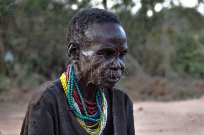 An elderly woman with beads around her neck