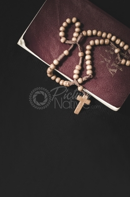 Bible and rosary on a black background