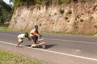 Boys ridding a wooden bike