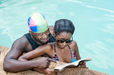 Couple reading a book from the swimming pool