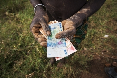 Dirty hands holding Ugandan notes