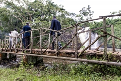 Men crossing a wooden bridge near a waterfall