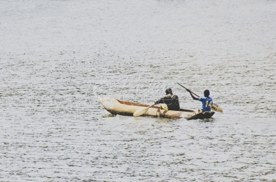Men in wooden boat move through Lake Bunyonyi, Kabale, Uganda