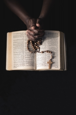 Praying hands, bible and rosary