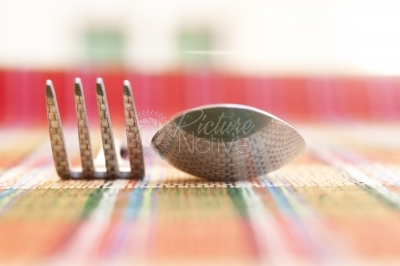 Reflection of texture of a mat on spoon and fork