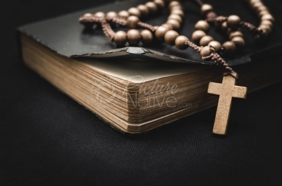 Rosary and bible on a black background