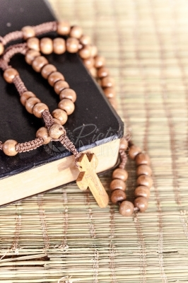 Rosary and bible on a mat texture background
