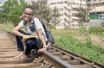 Teenager seated on a rail line