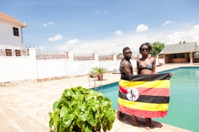 Two swimmers with the Uganda flag at the pool