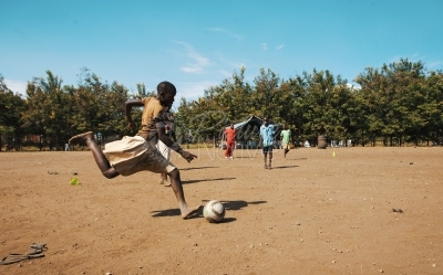Young girl kicking football