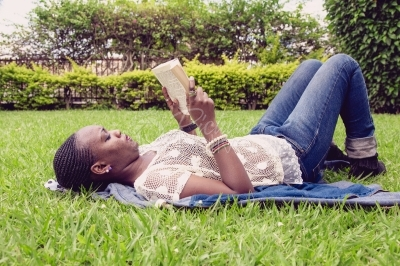 Young woman reading a book from the park